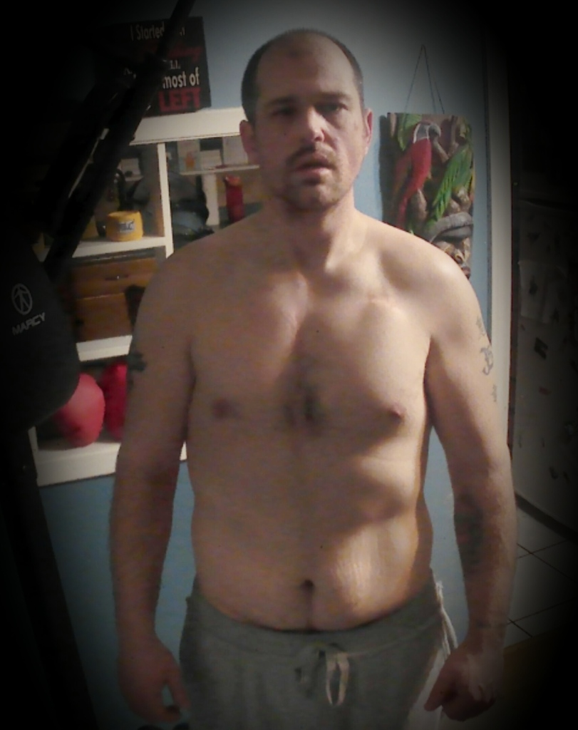 Grown man, before workout.  standing in front of a blue wall.  front view.